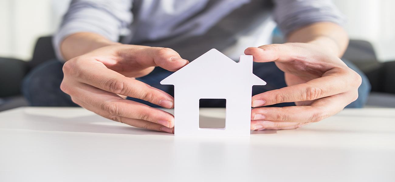 businessmen hold house model in hand