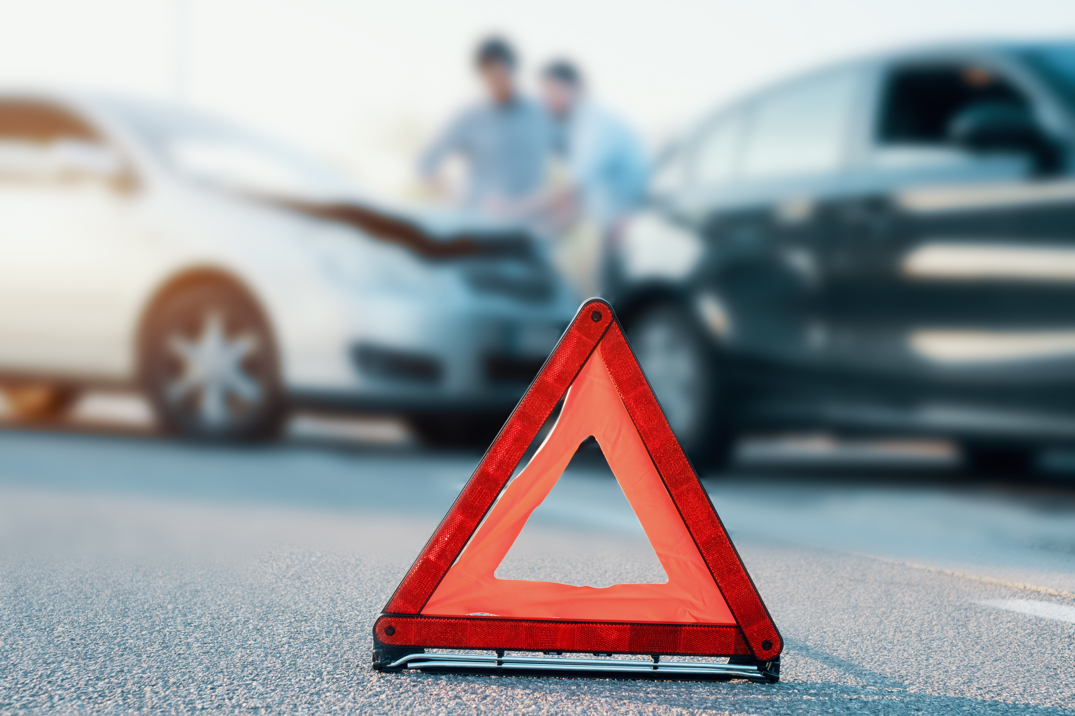 Two men reporting a car crash for the insurance claim,main focus on red triangle