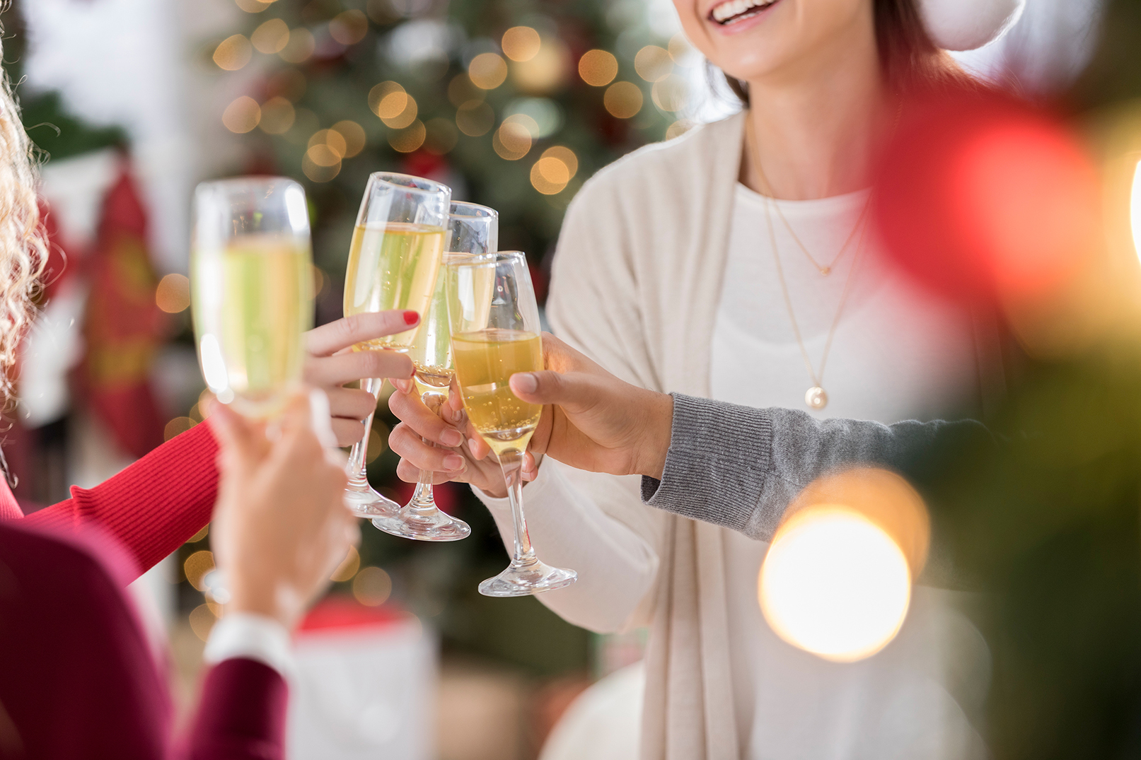 A group of friends toast the Christmas or New Year holiday. They are holding champagne flutes.