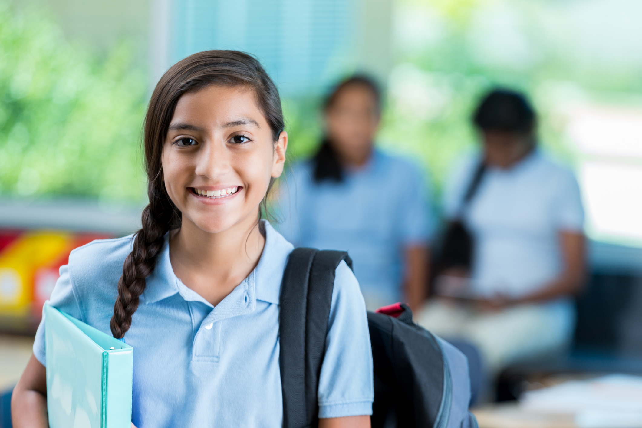 Cheerful Hispanic private middle school student smiles before class. She is standing in her classroom. He has a braid and is wearing a backpack and a school uniform. Students are in the background talking.