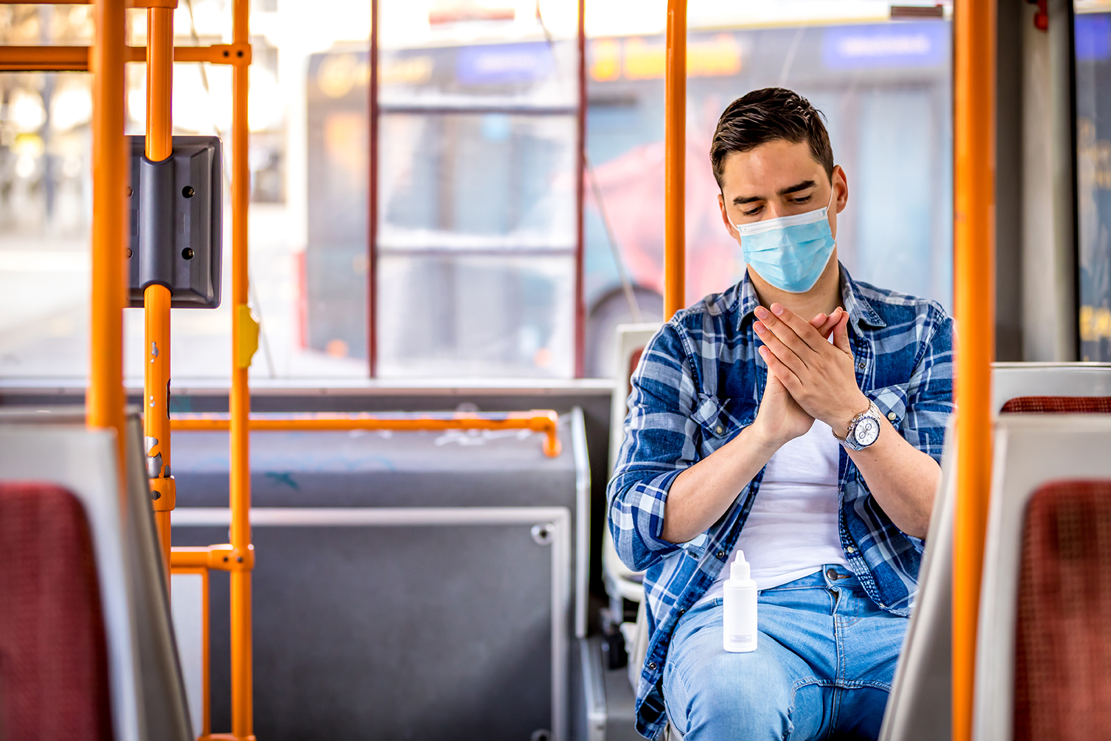 Image of  man in bus wearing medical face mask to protect coronavirus Covid-19 virus, pollution, face masks travelling during global health emergency, bird flu, respiratory problem, viral pneumonia, SARS, illnesses, quarantine and diseases