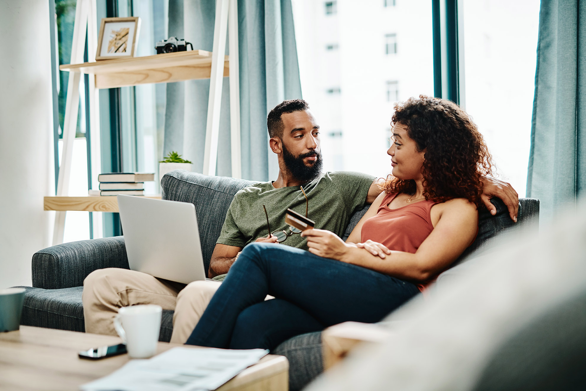 Shot of a young couple using a credit card while going over their finances at home