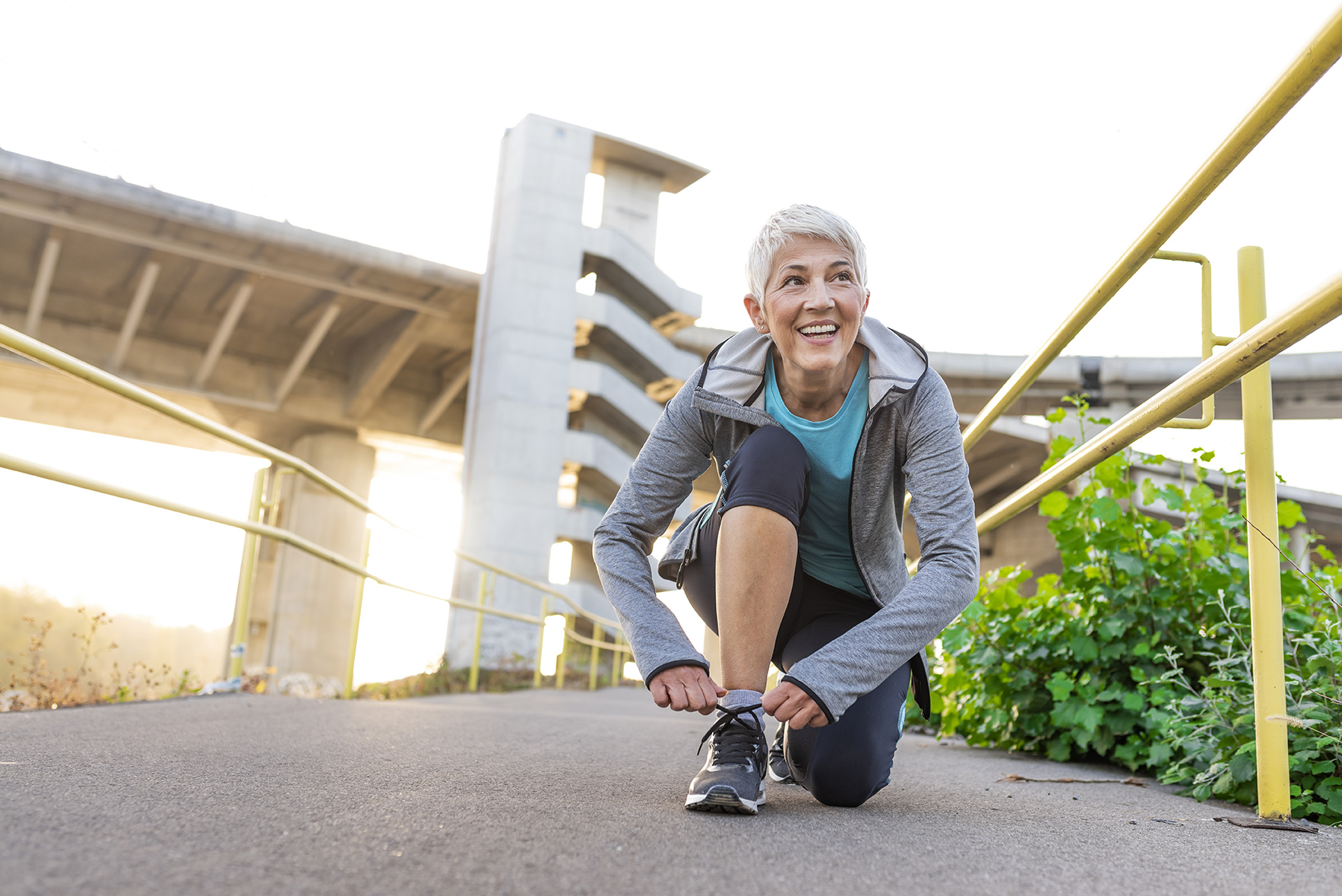 Healthy lifestyle and sport concepts, Photo of Fitness sport mature gray hair woman runner jogging, smiling female runner jogging exercise benefit workout in a Park, tying laces of running shoes before training. Woman tying laces on her sneakers at sunset. Runner having rest while looking away. Sport concept.