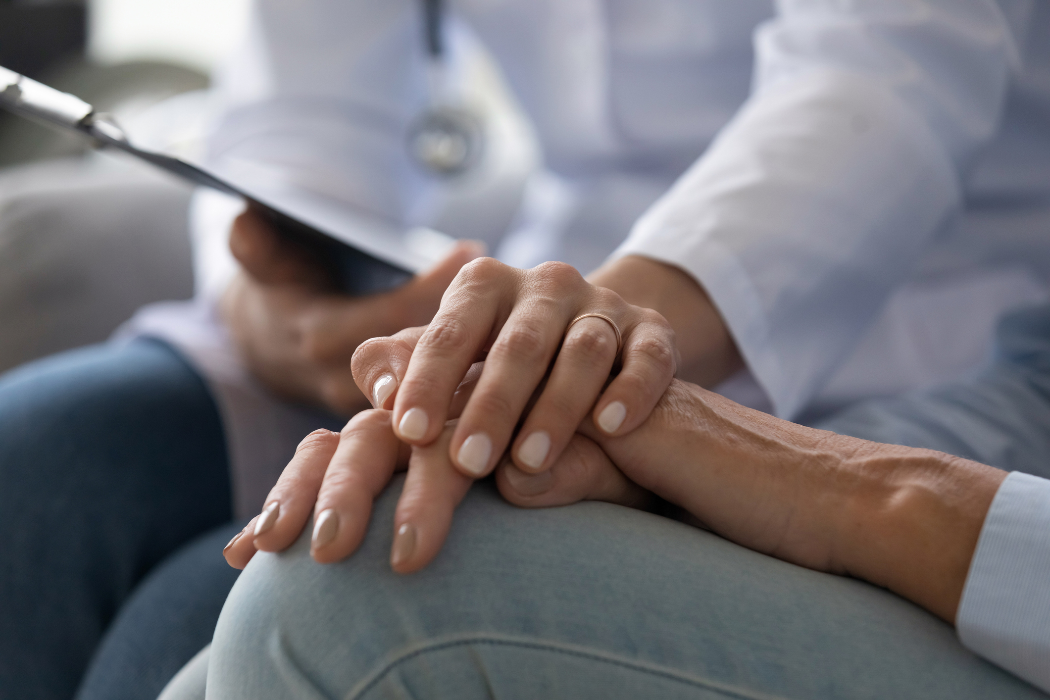 Young woman doctor nurse wear white medical uniform holding hand of senior old female grandmother patient having disease health problem give support help empathy and comfort concept, close up view