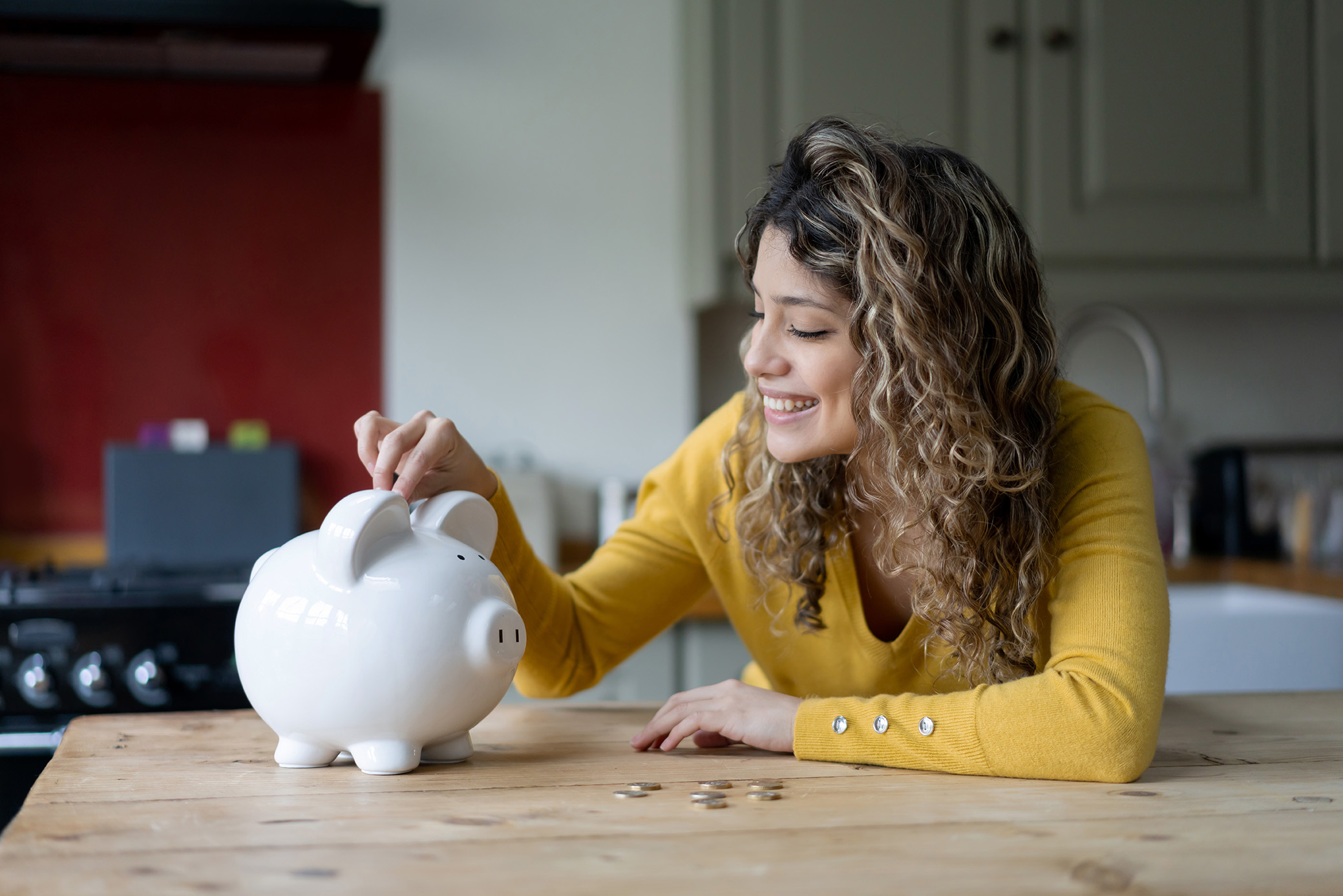 Cheerful young woman with curly hair at home saving coins into her piggybank smiling
