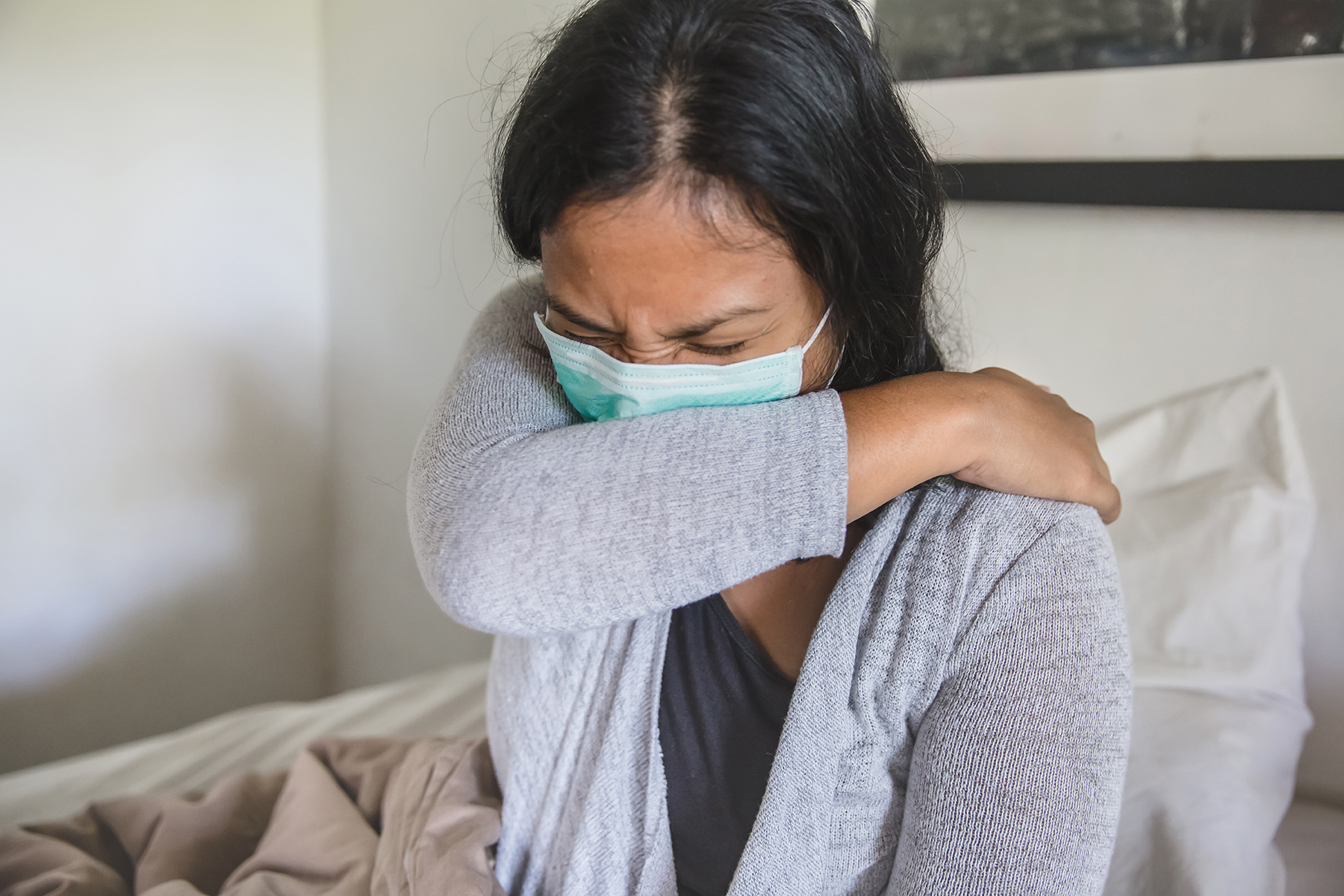 Portrait shot of Asian woman sick in bed,  covering cough with elbow, during home quarantine Covid 19
