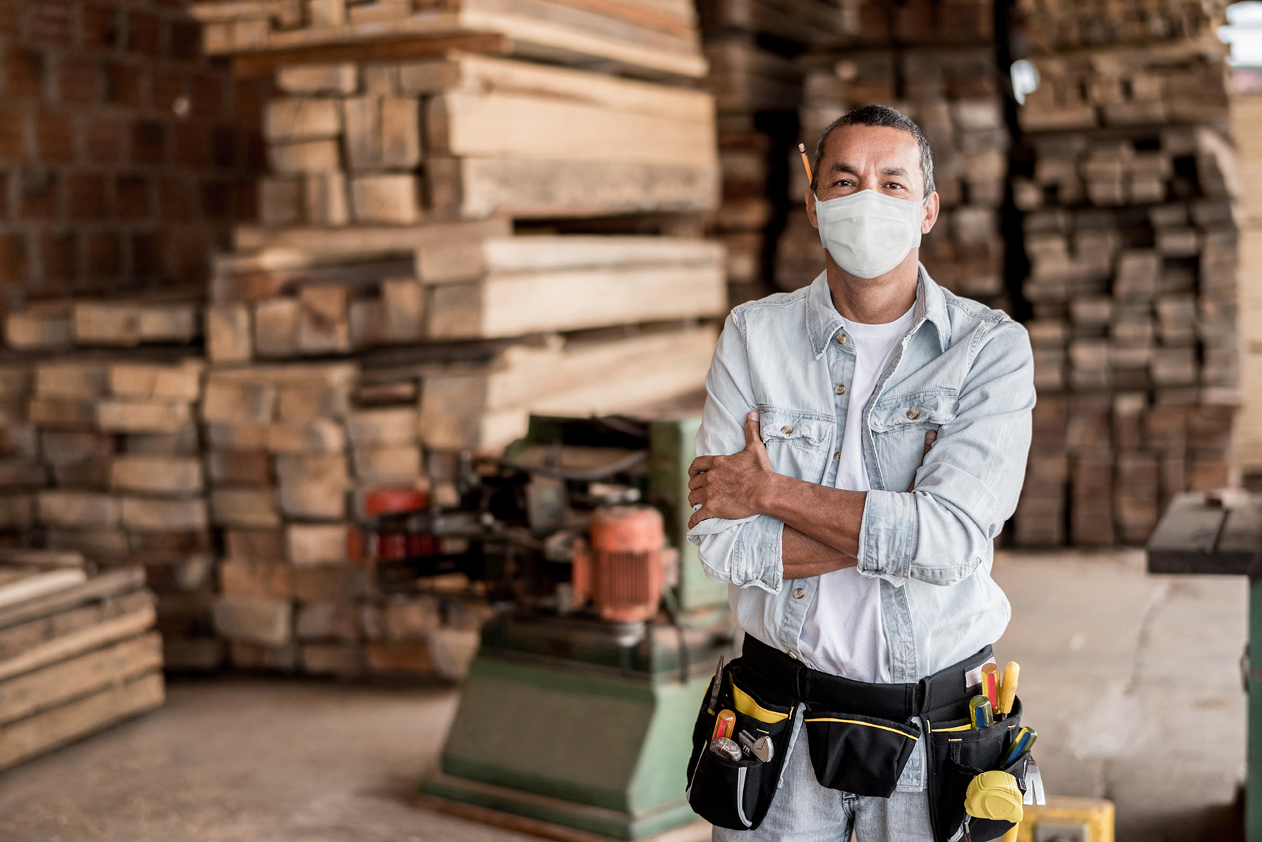 """Happy Latin American carpenter working at his workshop wearing a facemask to avoid coronavirus -"""" pandemic lifestyle concepts"""