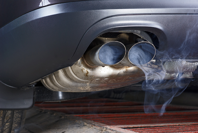 Exhaust pipe of a car - blowing out the pollution. Exhaust pipe coming out of the car with its exhaust. View from below, see the bottom of the exhaust pipe silver. Visible rear bumper eclipse of gray.