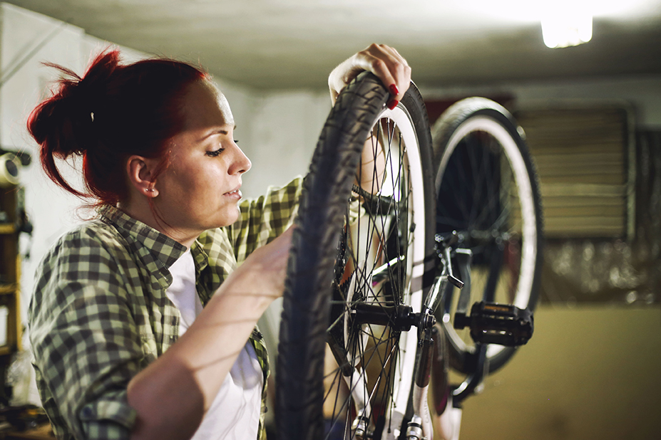 Young woman bicycle mechanic is repairing a bike in the workshop