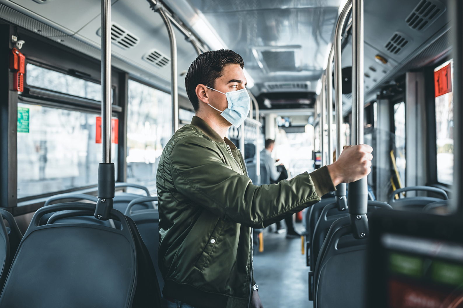 Image of  man in bus wearing medical face mask to protect corona virus Covid-19 virus, pollution, face masks traveling during global health emergency, bird flu, respiratory problem, viral pneumonia, SARS, illnesses, quarantine and diseases