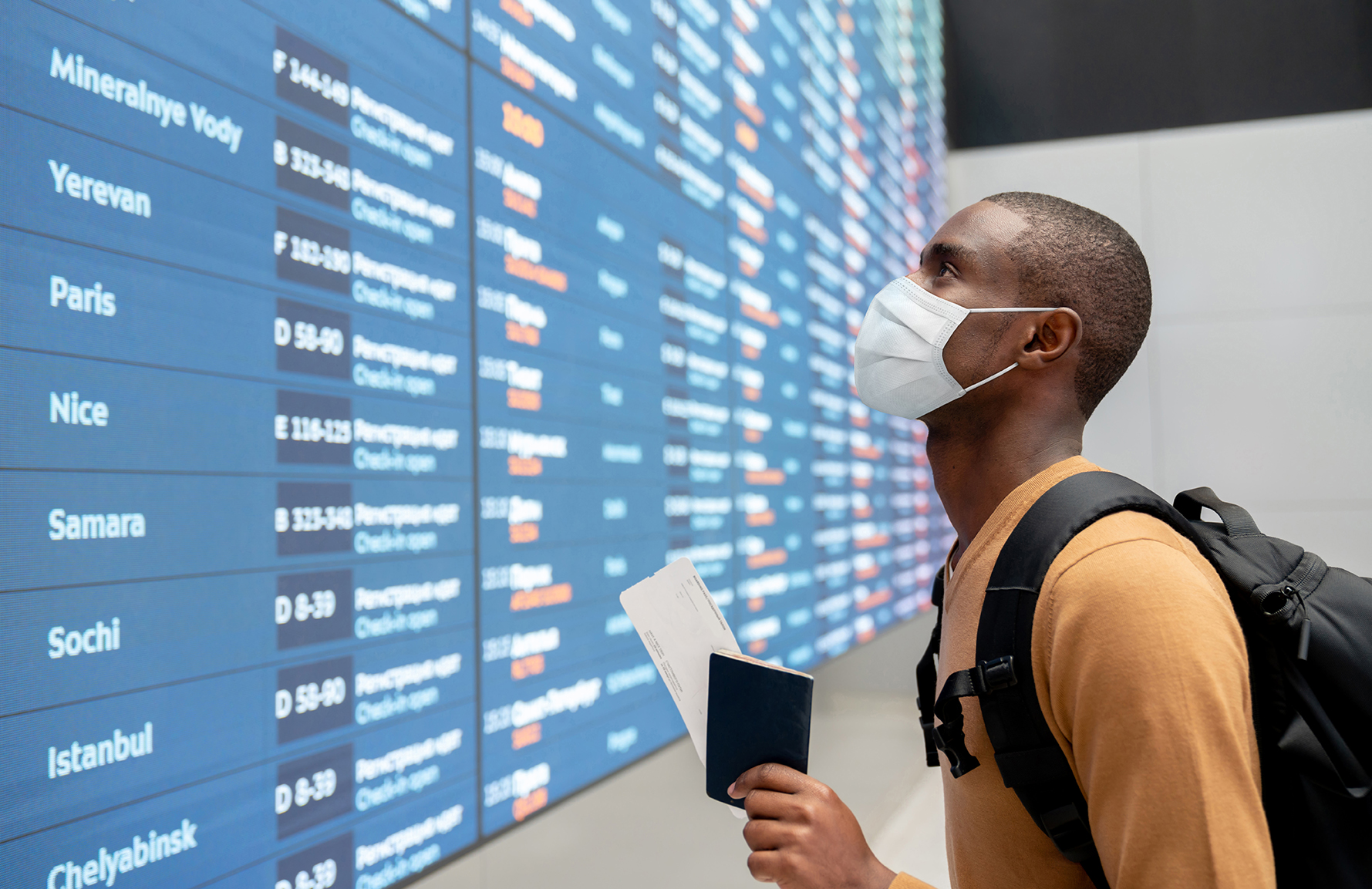 Portrait of a black male traveler wearing a facemask at the airport and looking at the flight schedule - travel concepts