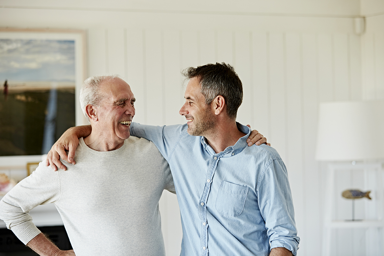 Smiling senior man with son standing arm around while looking at each other