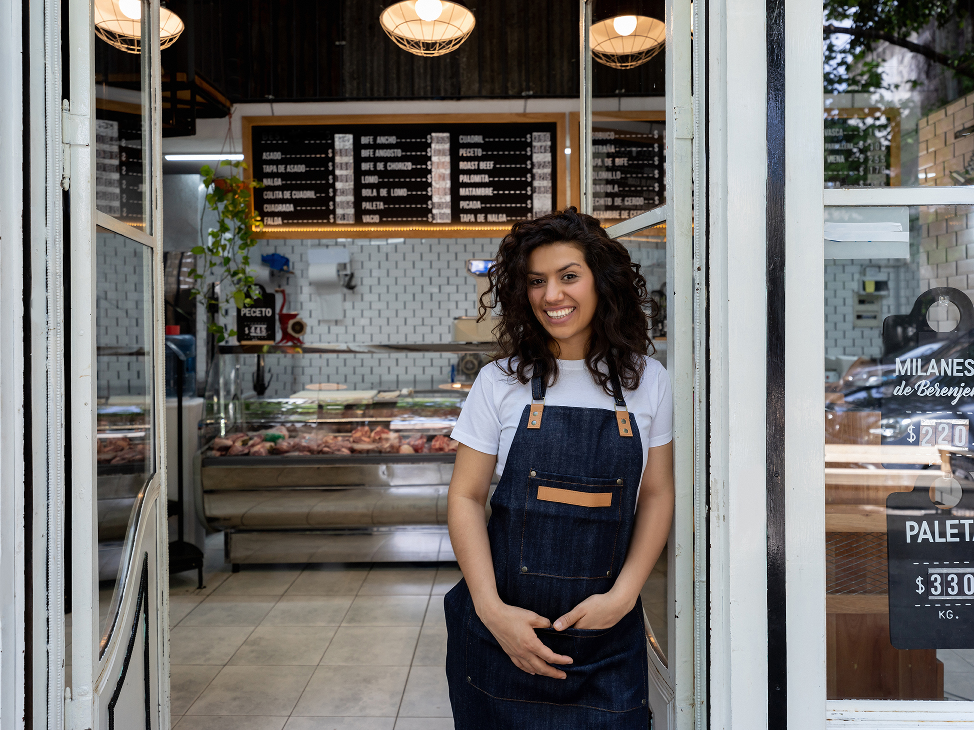 Portrait of beautiful young business owner of a butcher shop leaning against the entrance door smiling at camera very happy
