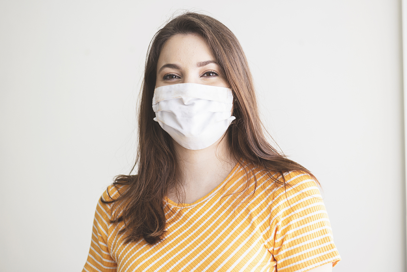 Photo ofa young woman wearing a protective mask smiling.