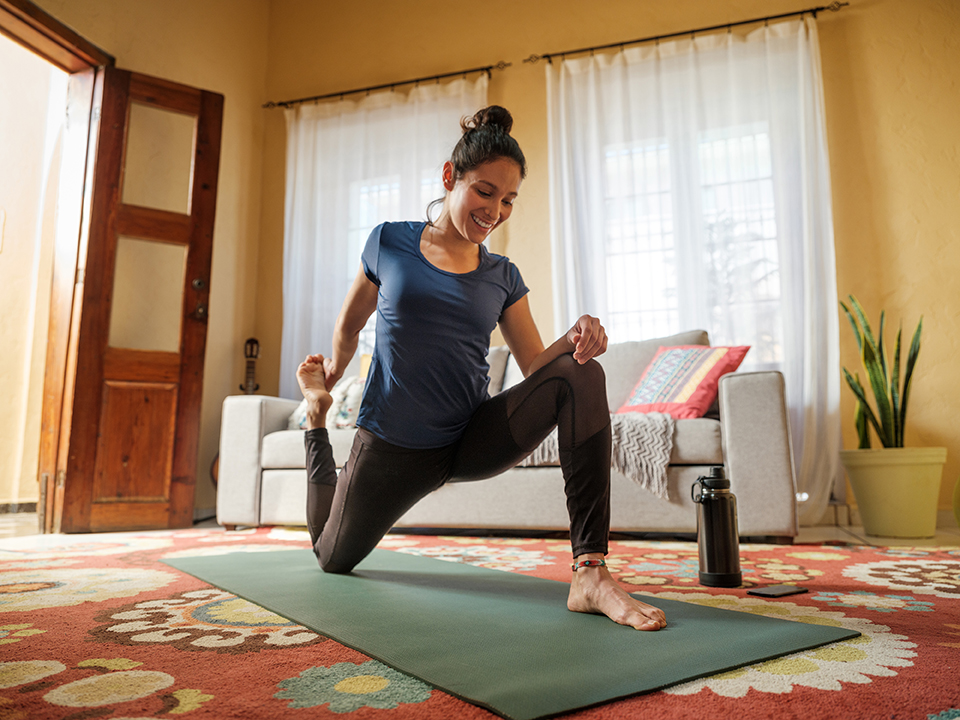A happy young latin woman stretching her legs on a mat in the living room, holding her leg and smiling.