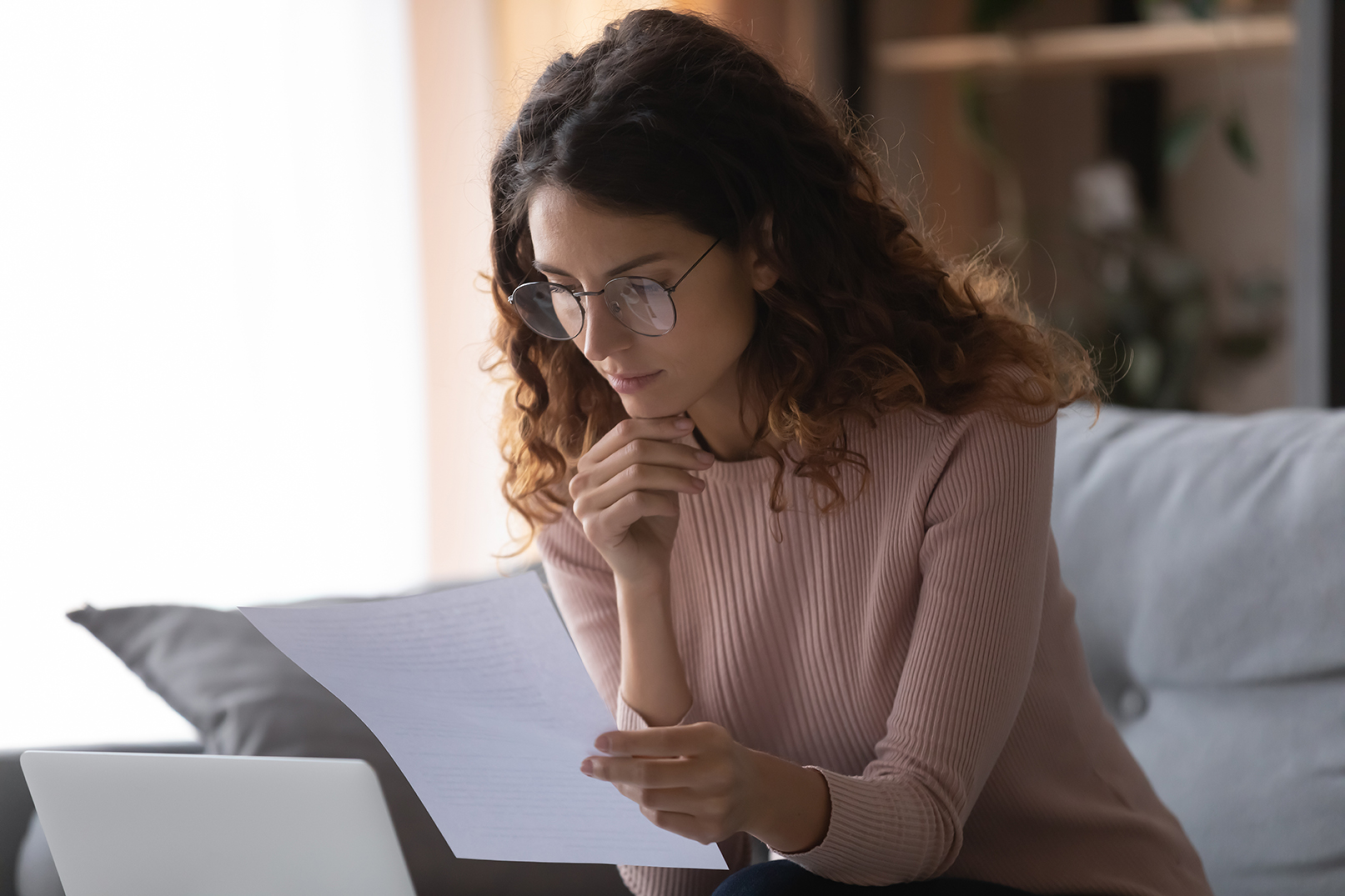 Focused woman wearing glasses reading document holding paper sheet close up, thoughtful businesswoman freelancer working with correspondence, checking financial documents, contract or notice at home