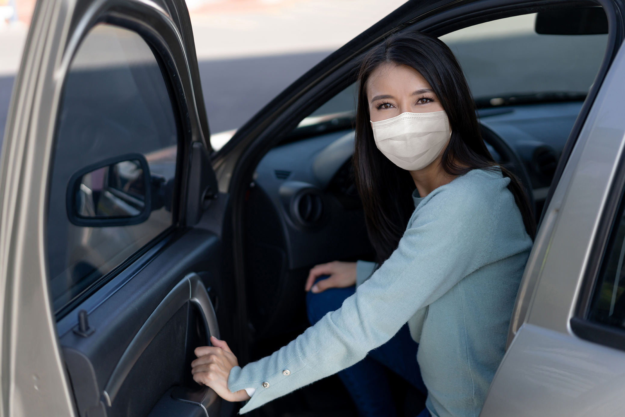 Portrait of a Latin American woman getting in her car wearing a facemask and looking at the camera - COVID-19 pandemic lifestyle