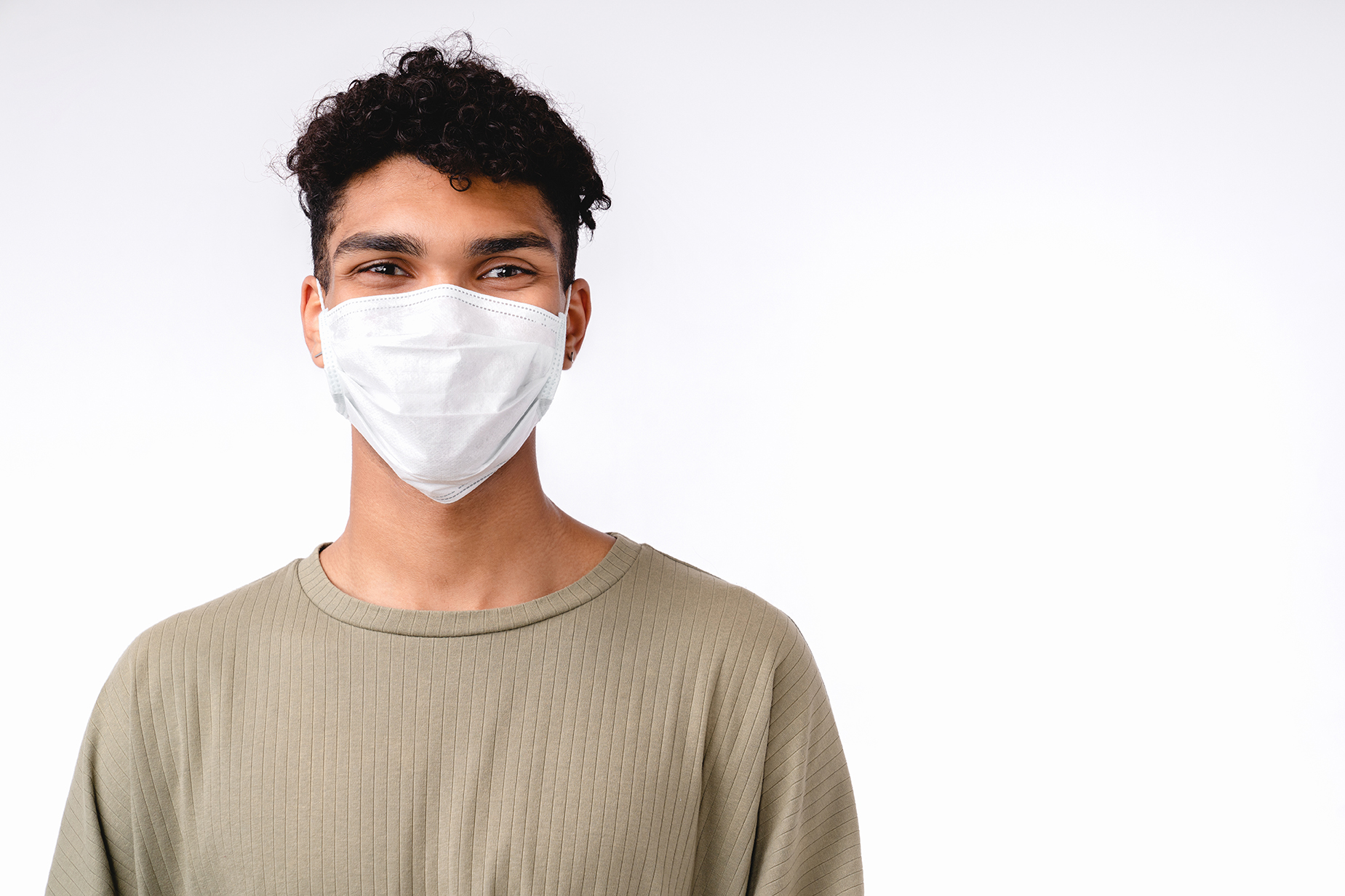 Handsome young mixed-race man wearing medical mask against coronavirus isolated over white background