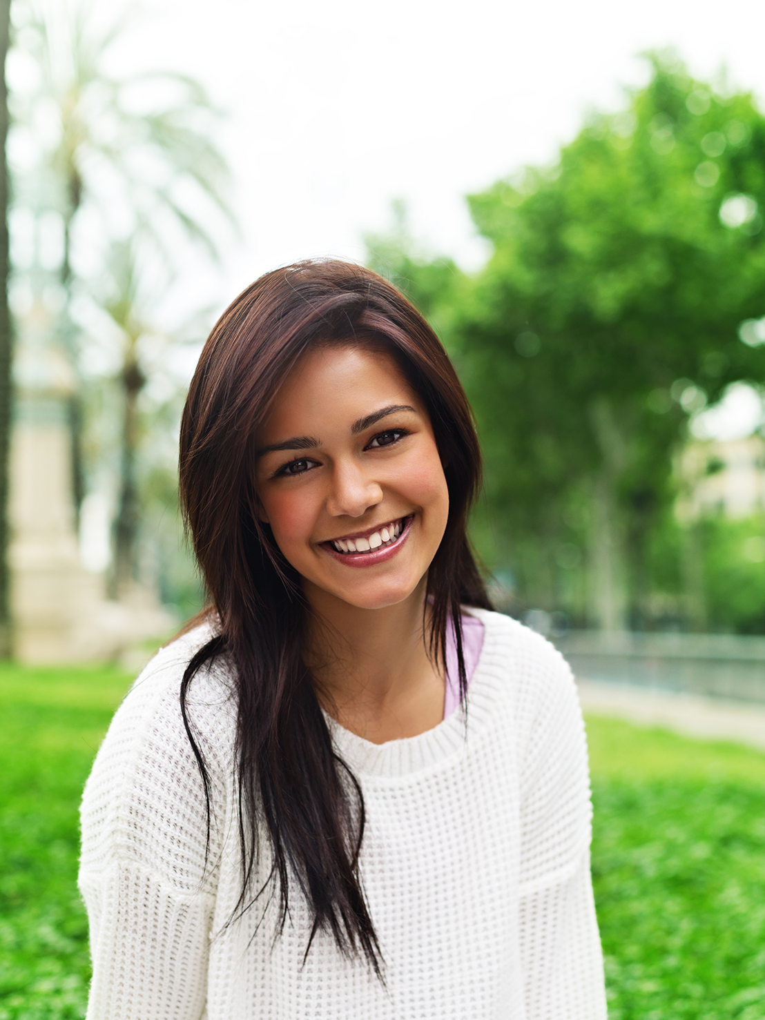Young woman looking at camera and smiling in a park.