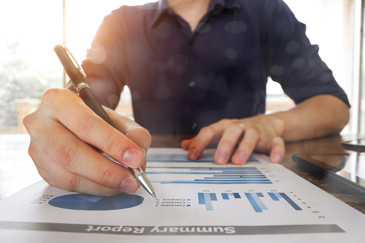 business man hand working with analysis graph chart document at office table - business and finance analysis concept