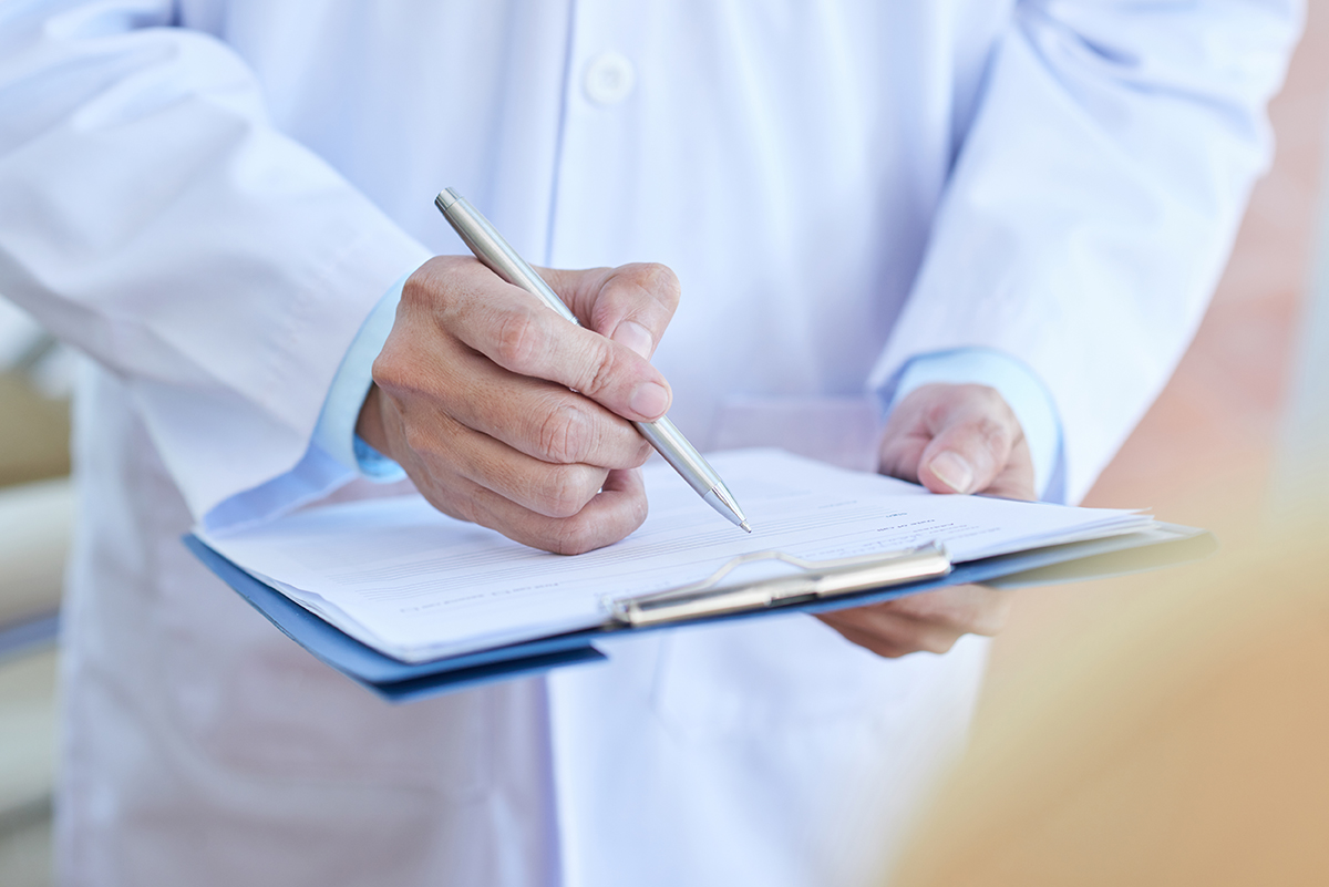 Close-up of male doctor in lab coat filling in medical form or prescribing a medicine