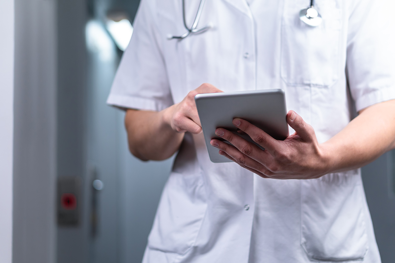 photo of male doctor in uniform with stethoscope coming out of the elevator and using computer tablet in hospital. Modern medical concept