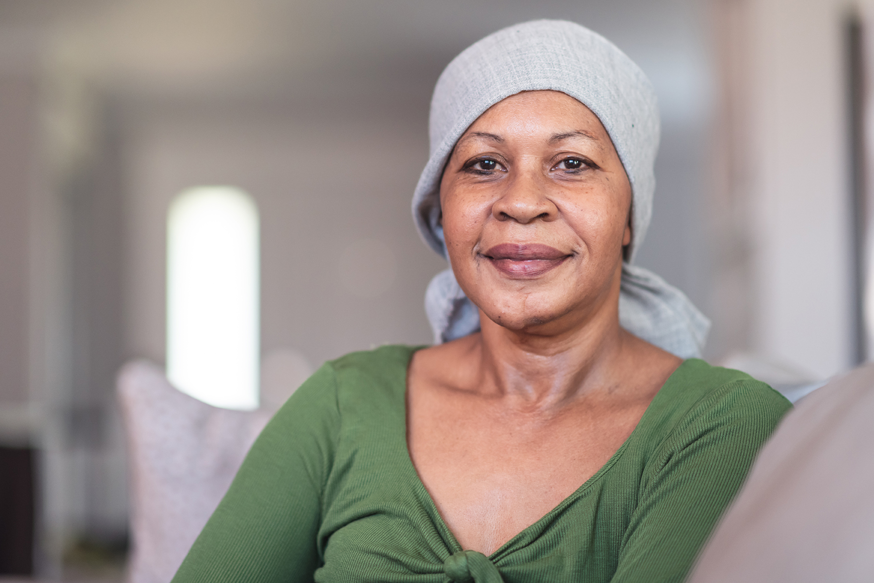 A mature black woman with cancer is wearing a scarf on her head. She is sitting at home in her living room. She is smiling directly at the camera. She is full of gratitude and hope for recovery.
