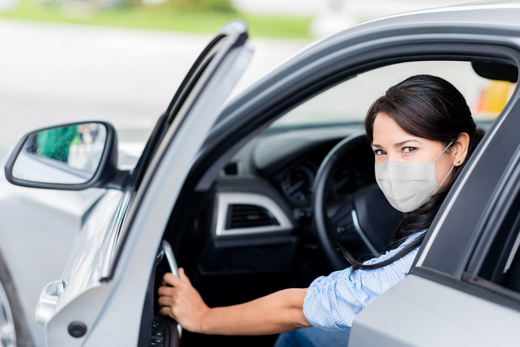 Woman getting out of the car to refuel it and wearing a facemask at the gas station – COVID-19 pandemic concepts