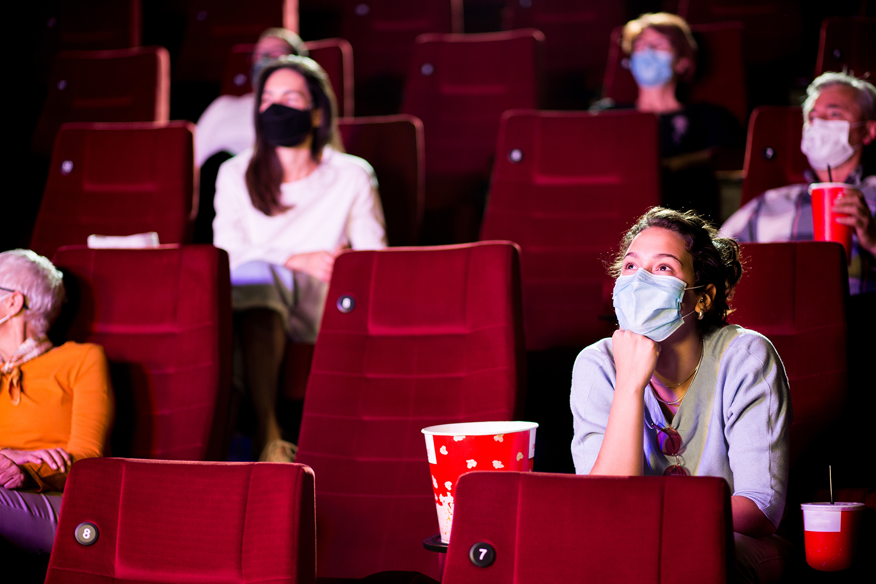 Audience at the cinema wearing protective face masks and sitting on a distance while watching the movie.